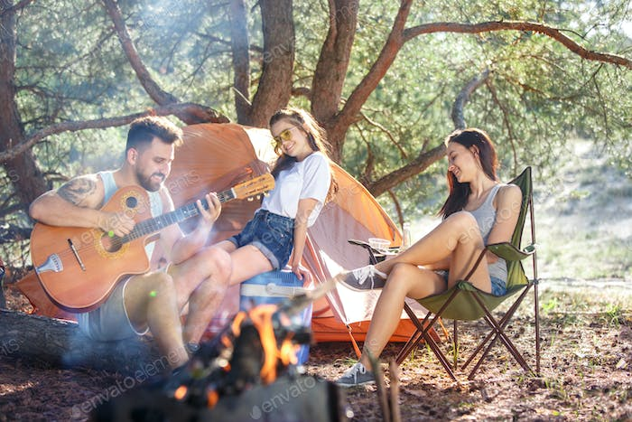 Party, camping of men and women group at forest. They relaxing, singing a song