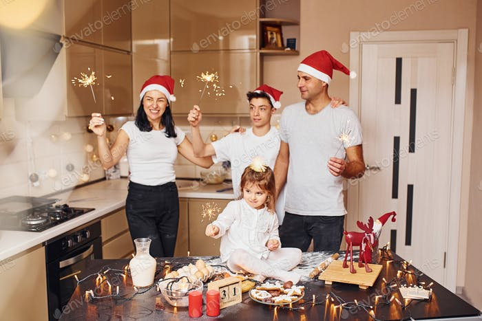 Cheerful family with sparklers in hands celebrating New year together on the kitchen