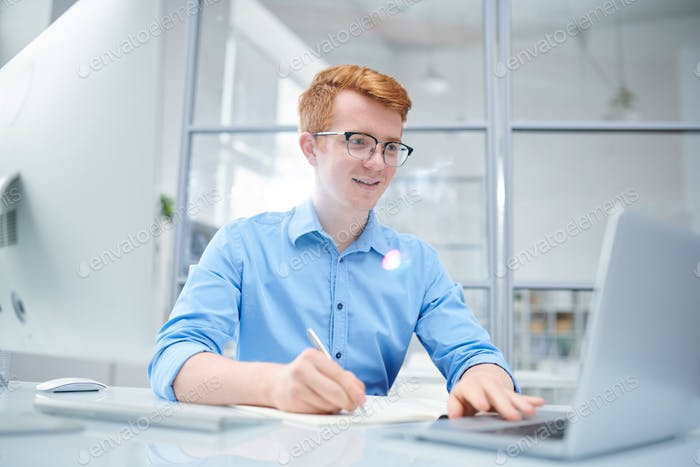 Young successful designer looking at curious online stuff on laptop display
