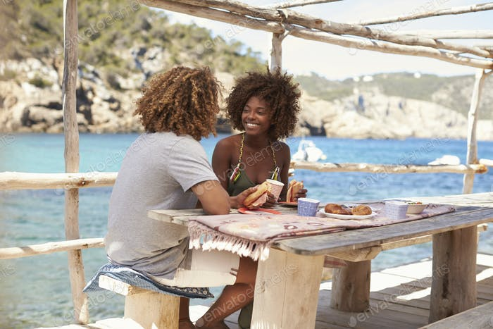 Mixed race couple having a meal by the sea, vertical, Ibiza