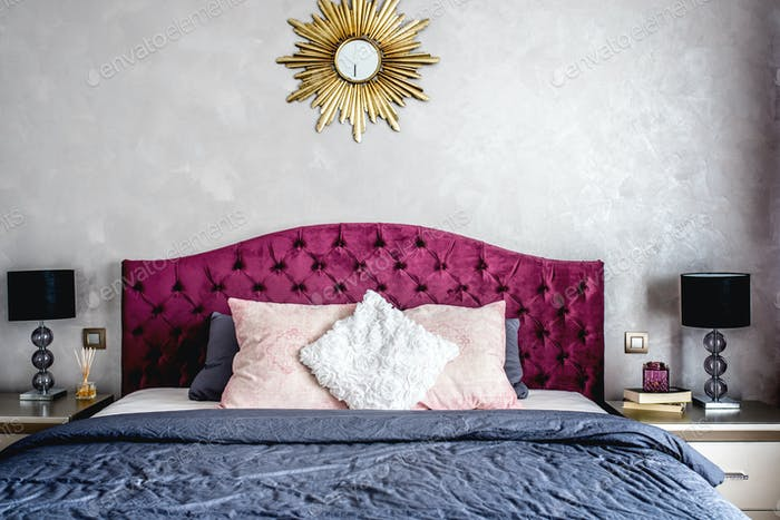 Luxurious bedroom interior with grey bedding and modern furniture. Bed details