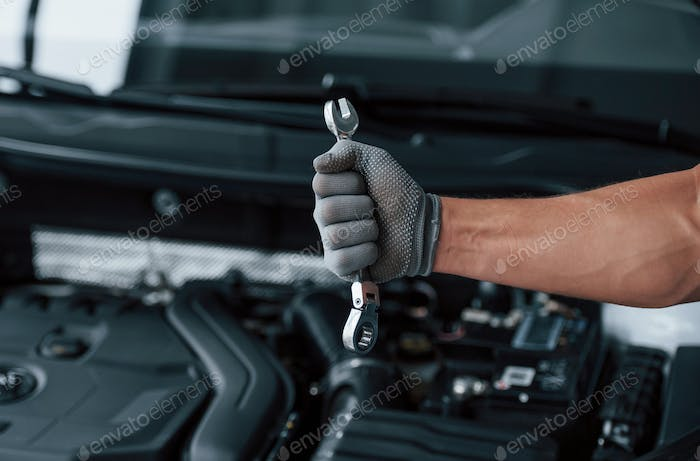 In the strong hand. Holds wrench in front of broken automobile