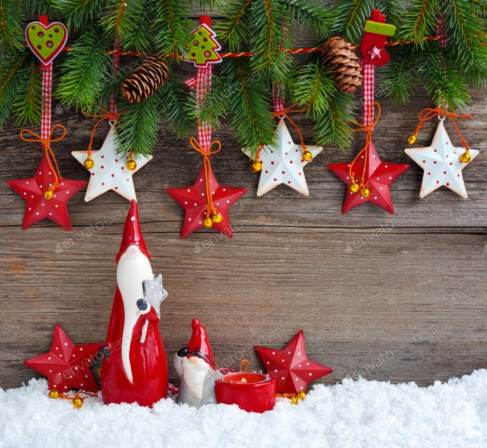 Christmas stars with gnomes and  branches of spruce on wooden background