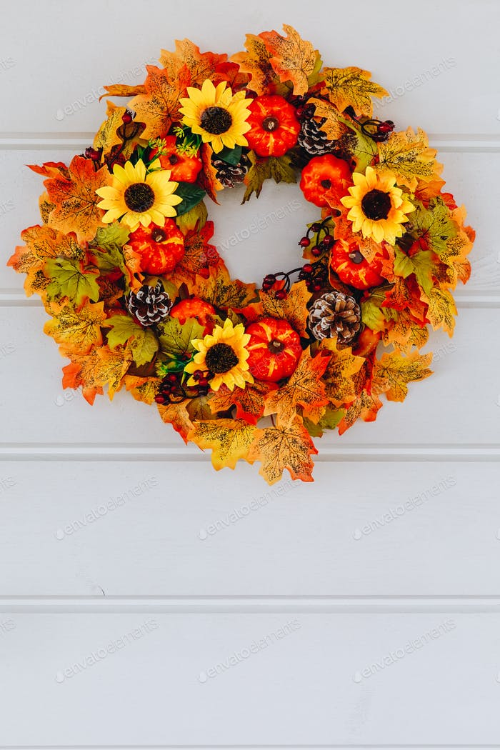 Autumn wreath with sunflowers, pumpkins and maple leaves on wooden door