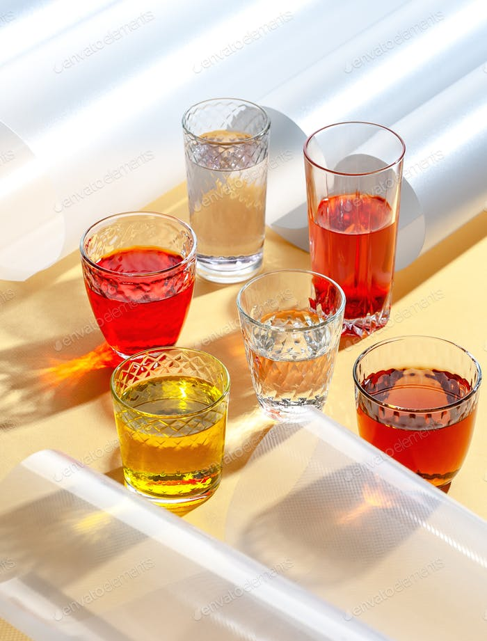 Glasbecher mit bunten kalten Getränken auf gelbem Hintergrund mit