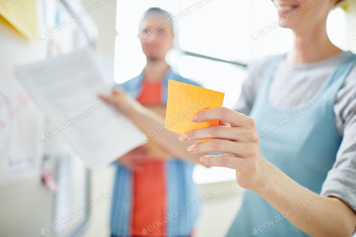 Manager holding adhesive note