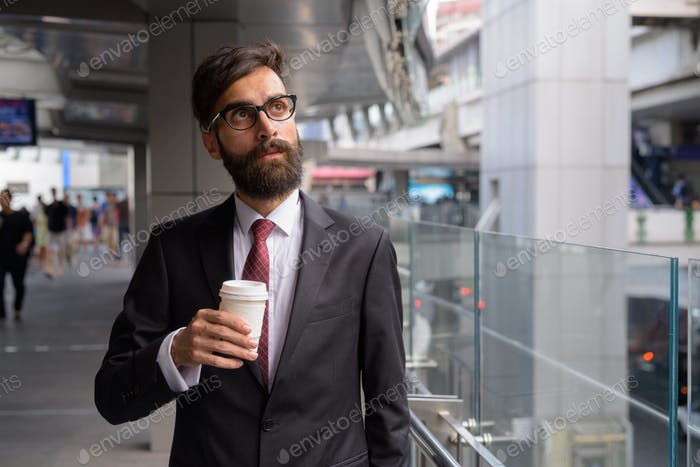 Young handsome bearded Persian businessman relaxing around the city
