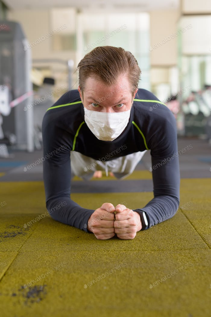 Face of young man with mask doing plank position on the floor at gym during corona virus covid-19