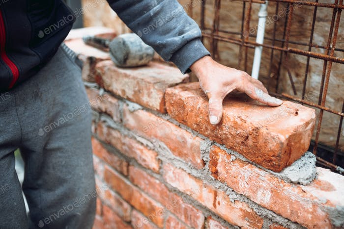 construction worker laying bricks and building walls on construction site