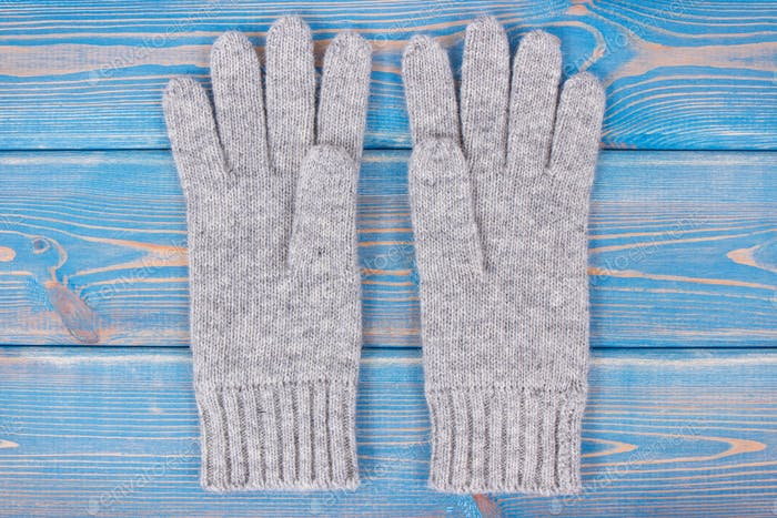 Pair of woolen gloves for woman on old blue boards