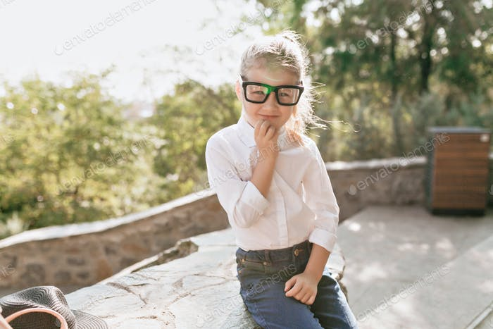 Little pretty girl in spectacles and white shirt prepraring for study outside and going to school