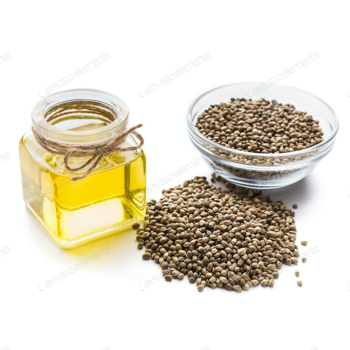 Hemp oil in bottle and bowl of seeds on white