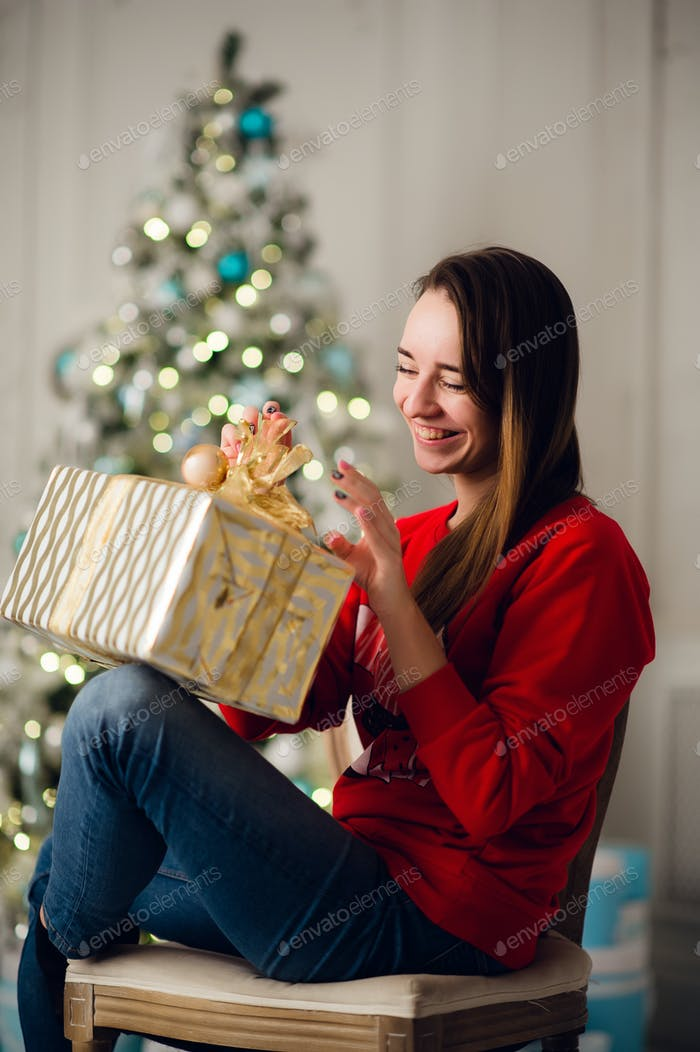 Young smiling woman in sweater holding a gift box celebrating winter holidays in decorated home