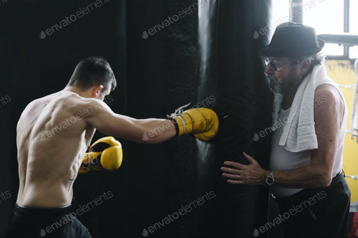 Trainer holding punch bag for boxer