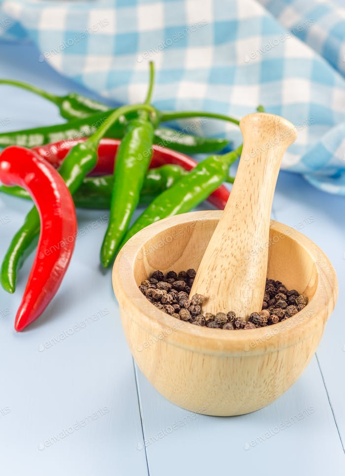Black pepper in wooden bowl and chili pepper