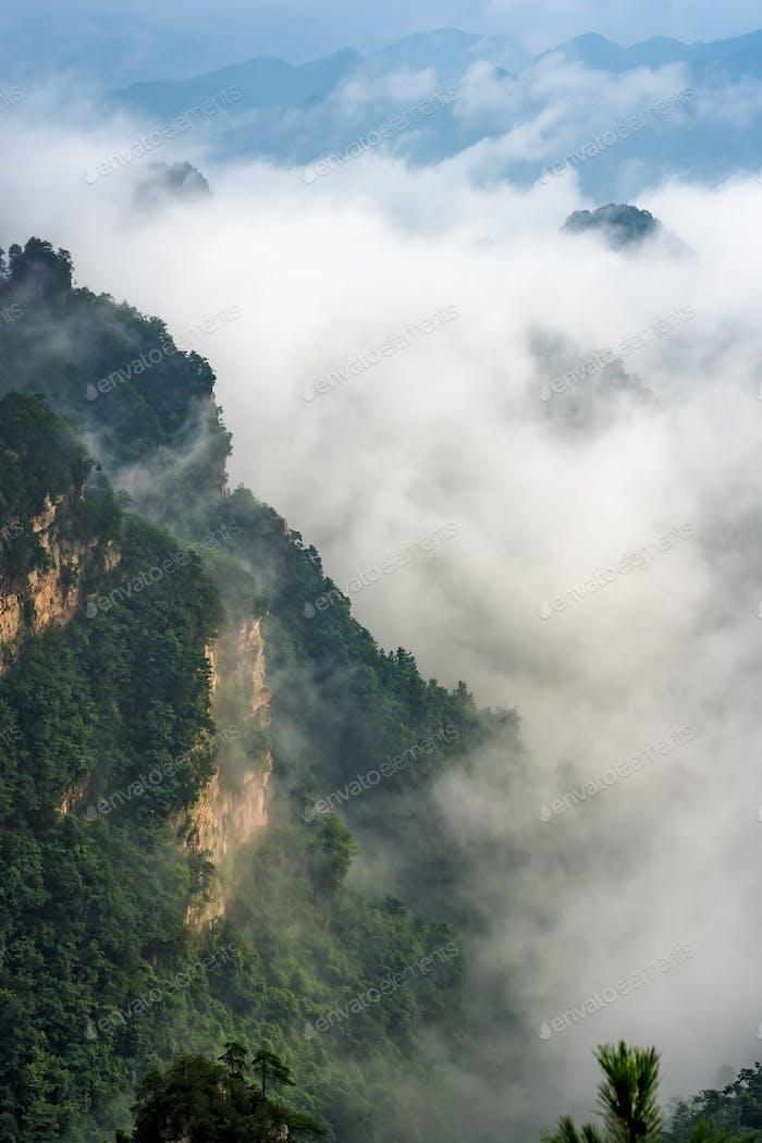 Low clouds engulfing stone pillars of Tianzi mountains in Zhangj