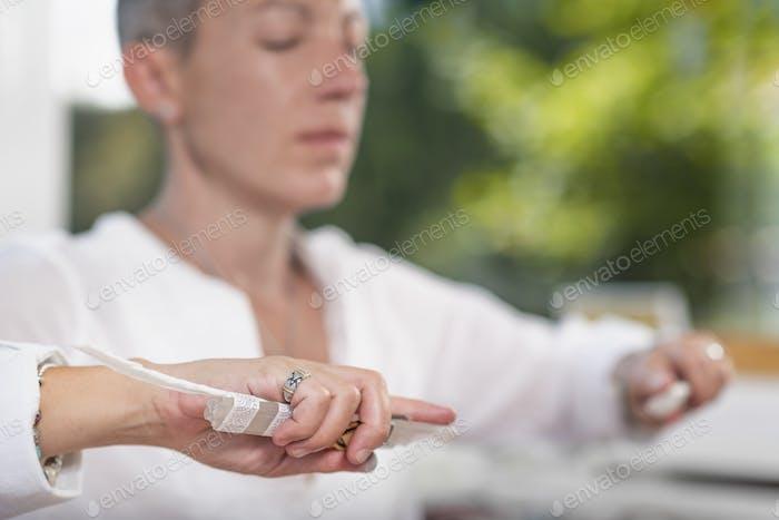 Schutzengel-Tugend, Hand eines spirituellen Heilers hält einen Kristall mit weißer Feder