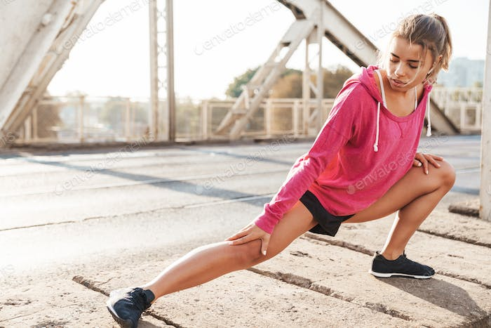 Sports fitness woman make stretching exercises outdoors.