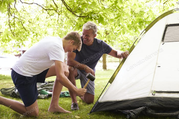Father And Teenage Son Putting Up Tent On Camping Trip