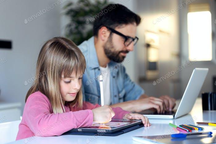 Hübsches kleines Mädchen Zeichnung auf ihrem digitalen Tablet, während ihr Vater mit Laptop zu Hause arbeitet.