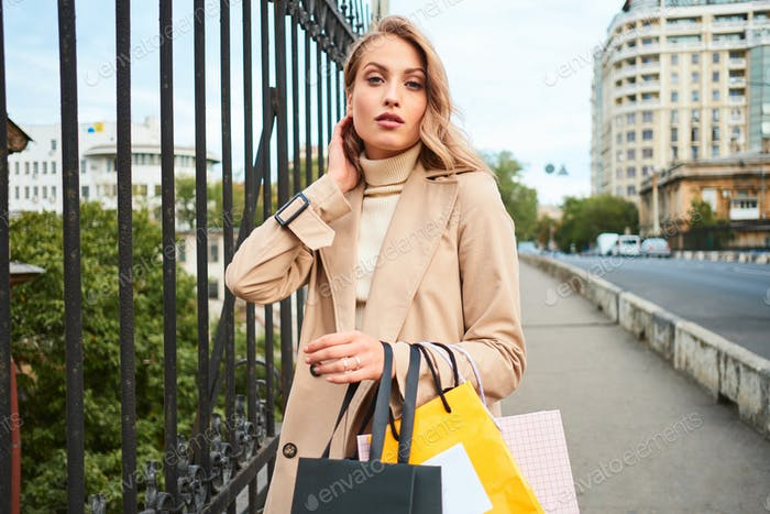 Beautiful blond girl in trench coat with shopping bags sensually looking in camera on city bridge