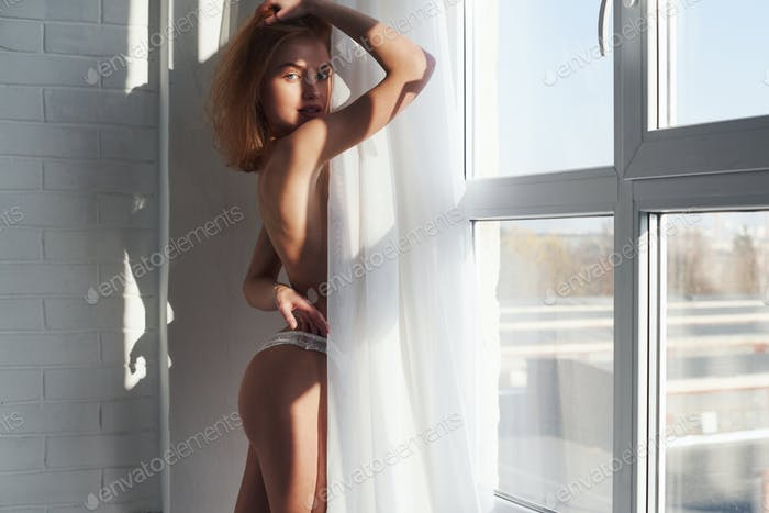 Girl with red hair is hiding her bare chest under the curtains. Sexy body type