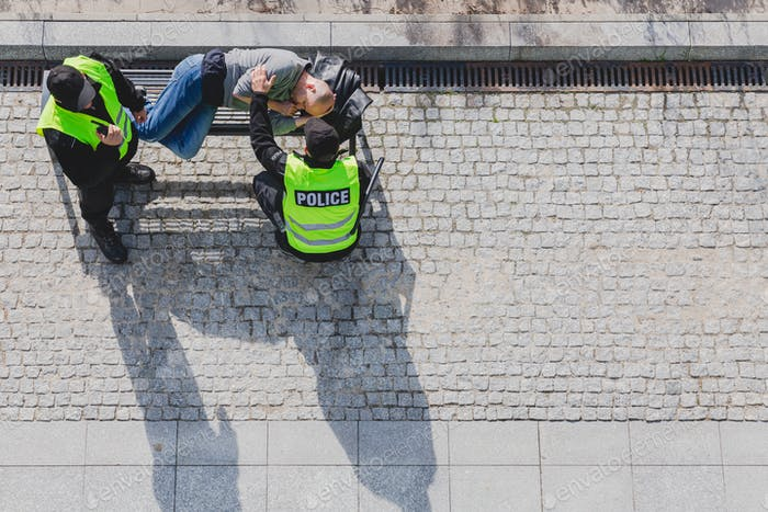 Police officers during patrol next to homeless man lying on the bench in the city
