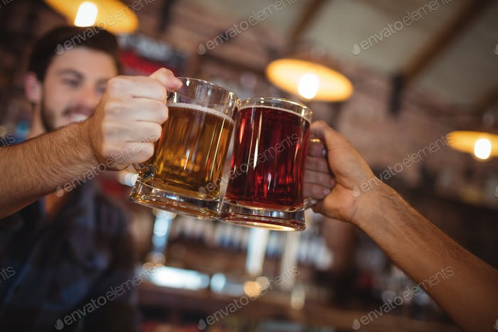 Two young men toasting their beer mugs