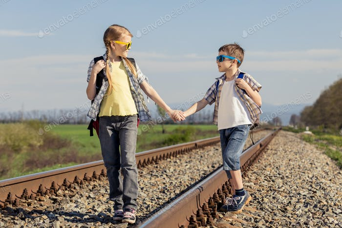 Happy brother and sister walking on the railway at the day time.