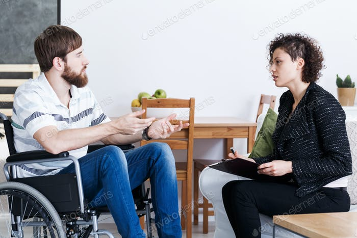 Man in wheelchair talking with psychotherapist