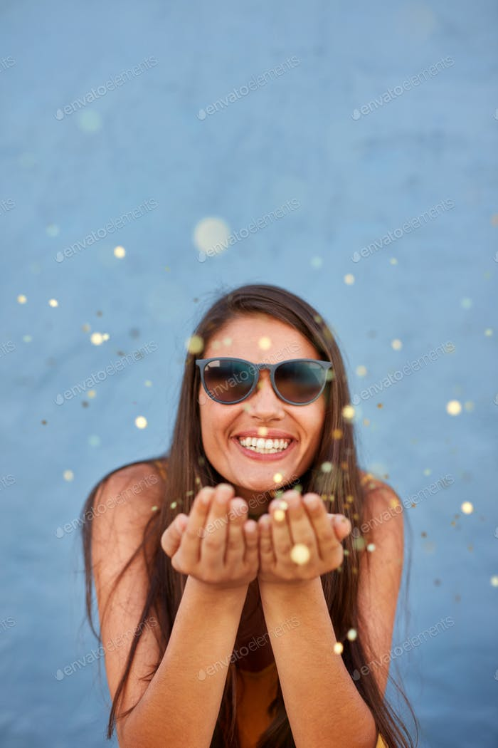 Young woman blowing confetti in the air and smiling