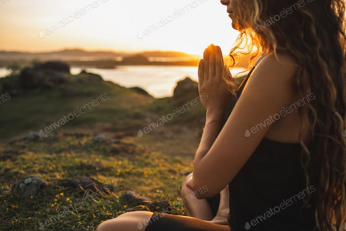 Woman praying alone at sunrise. Nature background. Spiritual and emotional concept