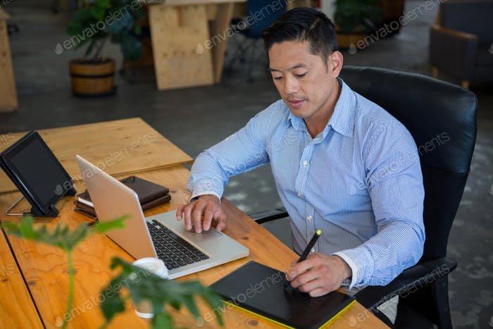 Graphic designer drawing on a graphic tablet while using laptop