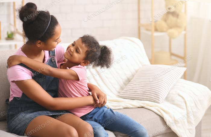 Happy african sisters embracing at home, sitting on couch