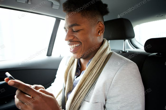 smiling young black man looking at cellphone while in backseat of car