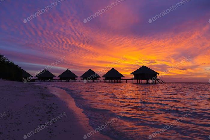 Sonnenuntergang auf den Malediven mit Blick auf die Lagune und Bungalows