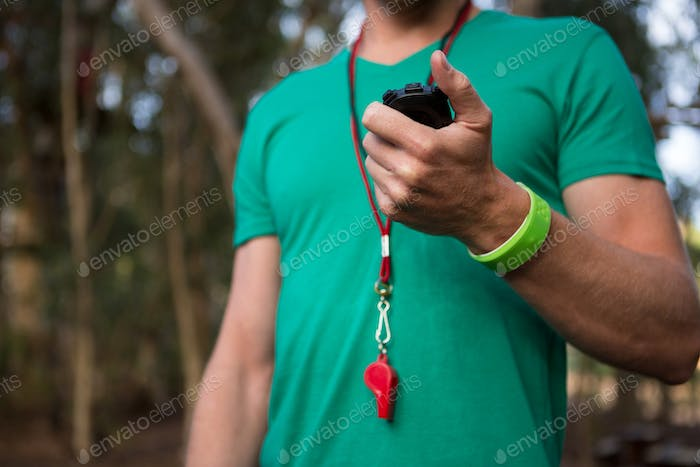 Trainer holding stop watch in his hand in the forest