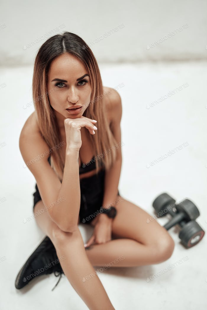 Female athlete with dumbells looking at camera