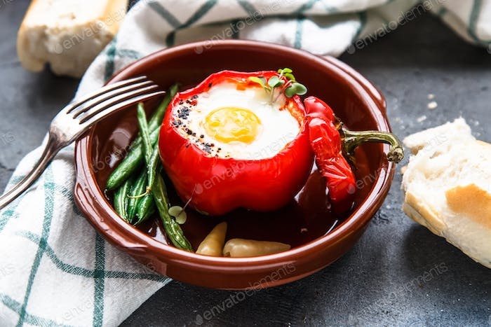 Baked bell pepper stuffed with egg and sausage on a plate, dark