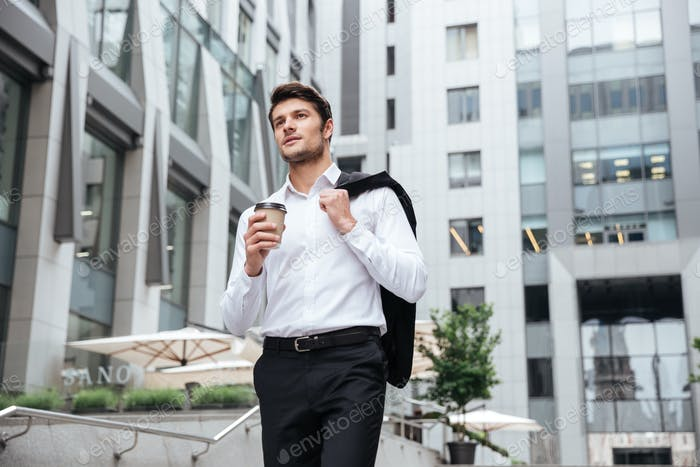 Businessman with cup of coffee walking in the city
