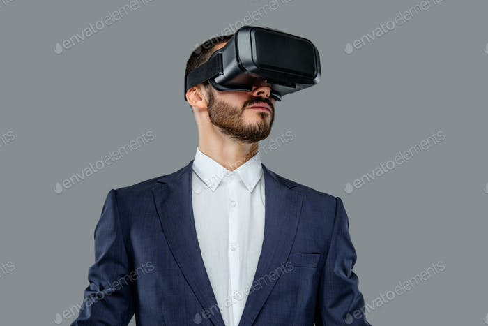Male in a suit with virtual reality glasses on his head.