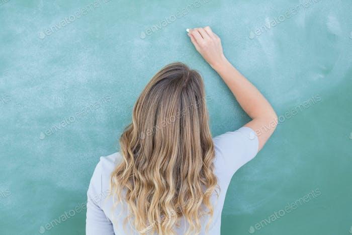 Teacher writing on blackboard in classroom