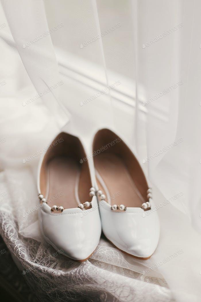stylish white shoes on window in soft morning light