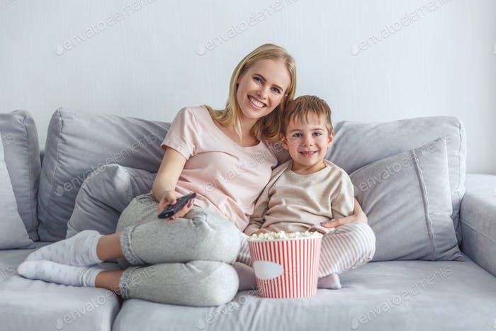 mother and son watching movie with popcorn together on couch
