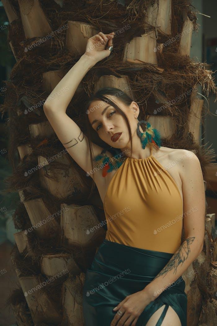 Fashionable woman portrait posing on palm tree steam