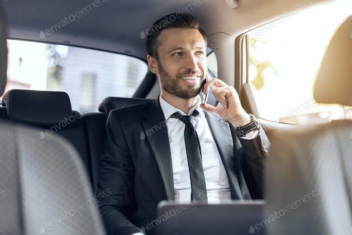 Glücklicher erfolgreicher Geschäftsmann im Gespräch am Telefon im Auto