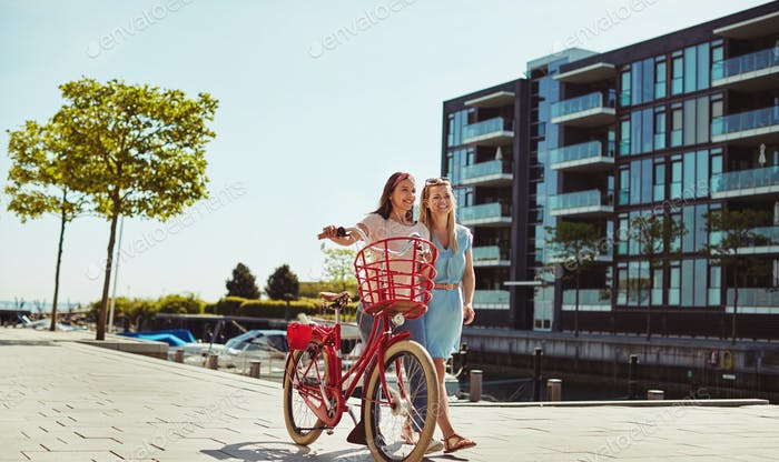 Girlfriends having fun walking with a bicycle through the city