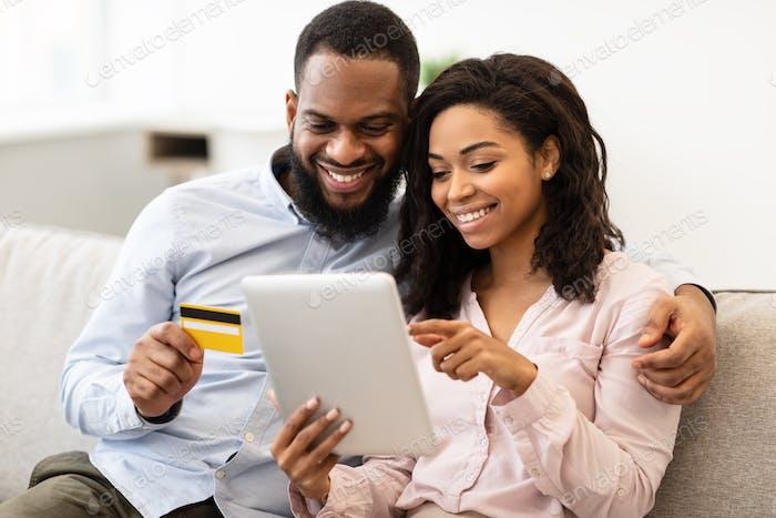 Pareja negra usando tableta y tarjeta de crédito de débito en casa