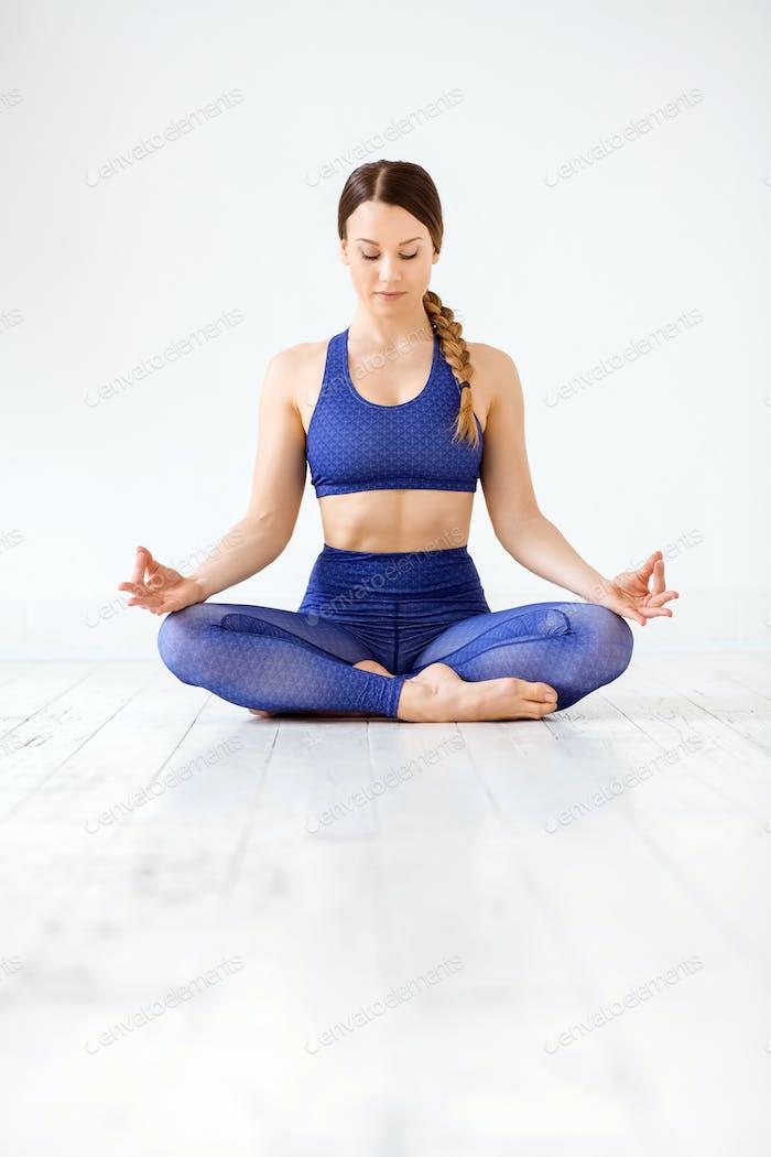 Fitte junge Frau meditiert in Yoga-Lotus-Pose