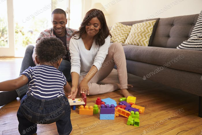 Parents And Son Playing With Toys On Floor At Home